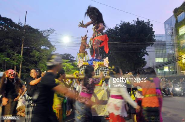 Indonesian women carry giant effigies in the form of the devil whose local name is 'Ogohogoh during a parade on the evening of the Day of Silence...