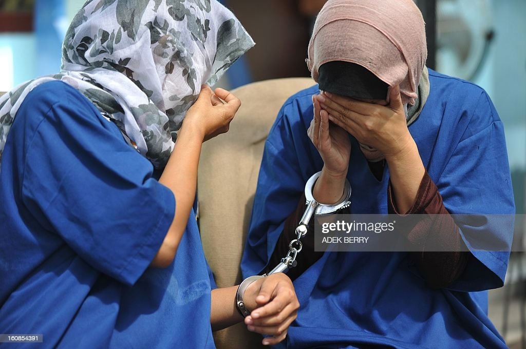 Indonesian women suspects for drug couriers cover their faces during a press conference in Jakarta on February 7, 2013. Indonesian authorities destroyed about 3 kilograms shabu confiscated during recents anti-drugs operation where syndicates are using women as drugs couriers. AFP PHOTO / ADEK BERRY