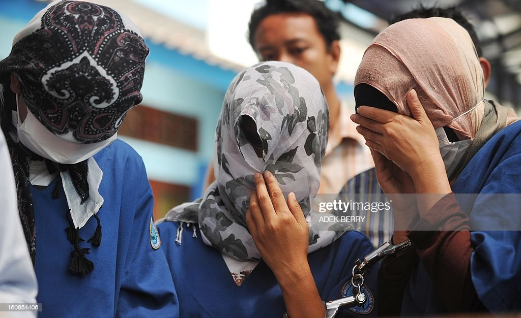 Indonesian women suspects for drug couriers cover their faces during a press conference in Jakarta on February 7, 2013. Indonesian authorities destroyed about 3 kilograms shabu confiscated during recents anti-drugs operation where syndicates are using women as drugs couriers.