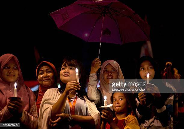 Indonesian women take shelter under an umbrella during a candlelight vigil for the victims of illfated Malaysian air carrier AirAsia flight QZ8501 in...