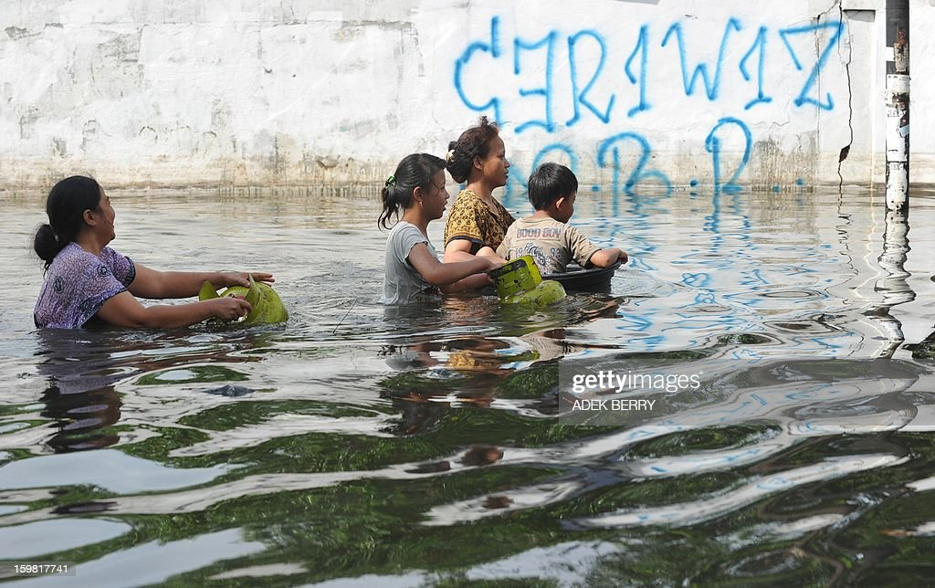 Indonesian women wade through a flooded street with a child to get free cooking gas in Jakarta on January 21, 2013. Companies and consumers have started to calculate damages and losses from the widespread floods that hit Jakarta on, claiming at least 15 lives a police spokesman said on January 19, displacing thousands from their homes and afflicting capital residents with water-borne illnesses, a local newpaper reported.