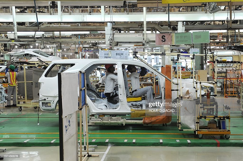 Indonesian workers inspect shells of Toyota vehicles at the assembly line of Toyota Motor's Indonesian unit, Toyota Motor Manufacturing Indonesia (TMMIN) plant in Karawang industrial center outside Jakarta on December 3, 2012. Japan's Toyota group announced in Tokyo on November 10, 2012 that it will invest about 1.3 billion USD over the next five years in expanding its vehicle production in Indonesia. Toyota Motor and its five affiliated firms are making the move 'considering the remarkable growth of the (Indonesian) market in recent years.' AFP PHOTO / ROMEO GACAD