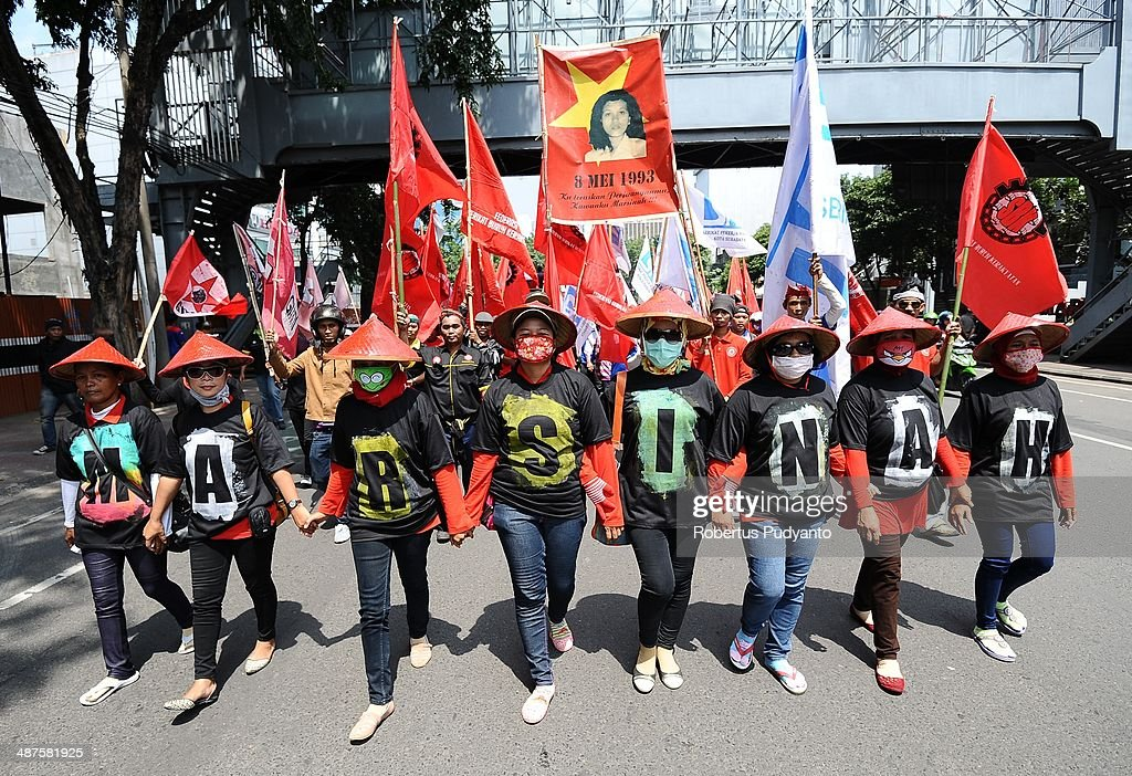 Indonesian workers march down the street to mark May Day on May 1, 2014 in Surabaya, Indonesia. Protesters across Indonesia have organised rallies to demand higher wages, as Indonesia recognises its first national labour day holiday.