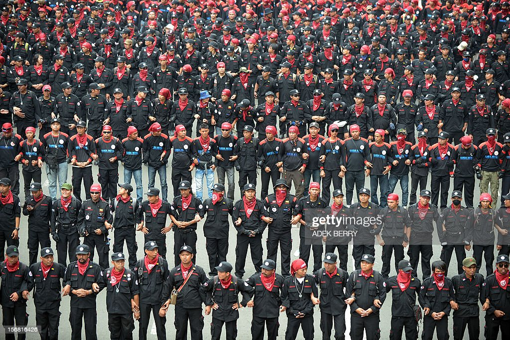 Indonesian workers march towards the Indonesian presidential palace during a rally in Jakarta on November 22, 2012. Thousands workers took to the street demanding Indonesia's government to increase their wages, to improve working condition and end the practice of outsourcing manpower.