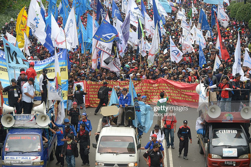 Indonesian workers march towards the presidential palace during a rally in Jakarta on November 22, 2012. Thousands workers took to the street demanding Indonesia's government to increase their wages, to improve working condition and end the practice of outsourcing manpower.