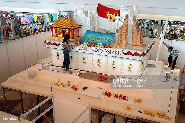 Indonesian workers put the finishing touches to a 8X6 wide and 5 meter high cake from Chinese Indonesian woman Nila Sari at a shopping mall in...