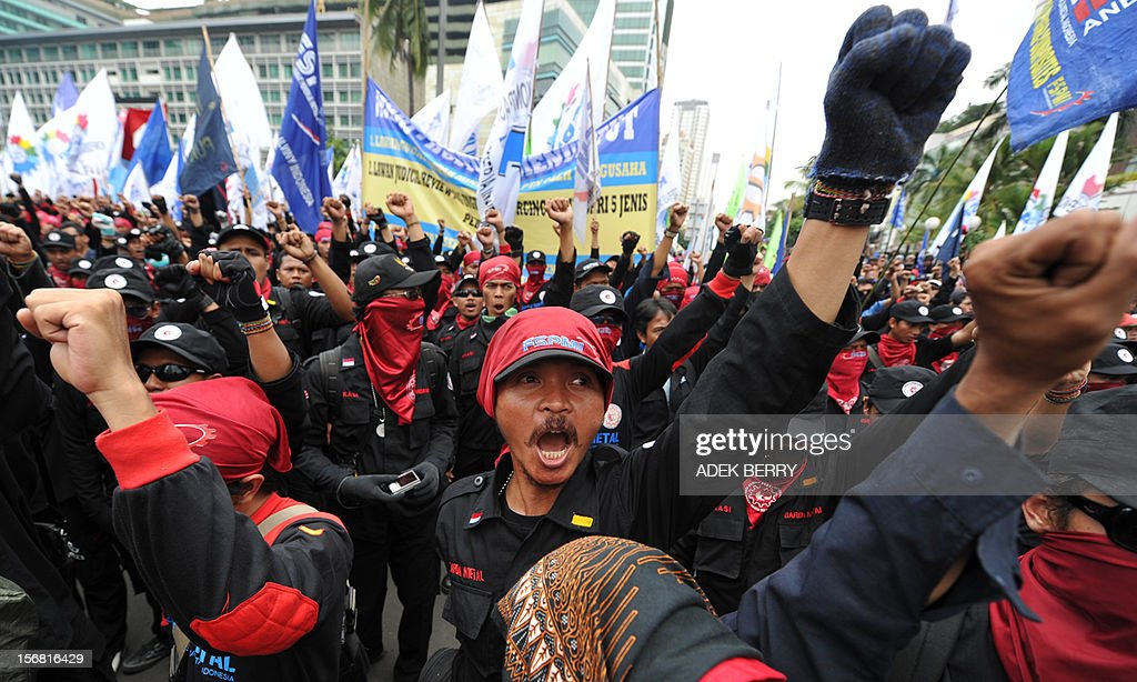 Indonesian workers shout slogans during a rally in Jakarta on November 22, 2012. Thousands workers took to the street demanding Indonesia's government to increase their wages, to improve working condition and end the practice of outsourcing manpower.
