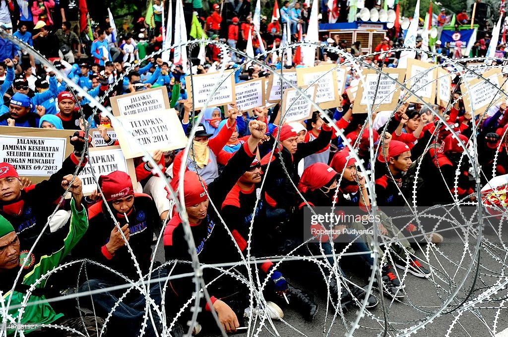 Indonesian workers sit behind barbedwire during a protest demanding higher wages on May Day on May 1 2014 in Surabaya Indonesia Protesters across...