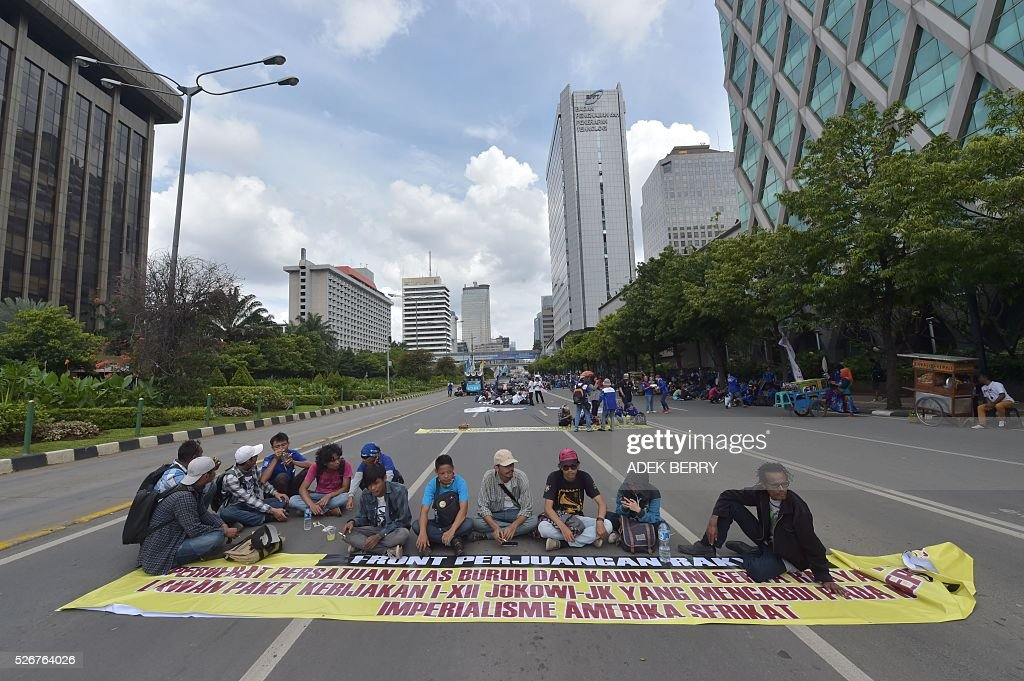 Indonesian workers sit on Jakarta's main road as they participate in a rally to mark May Day in Jakarta on May 1, 2016. Labourers and activists around the world marked international worker's day with marches demanding better working conditions, welfare and higher wages. / AFP / ADEK