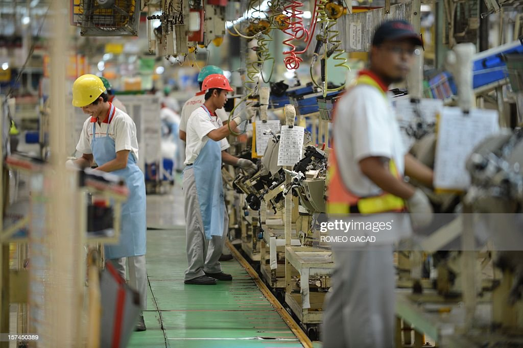 Indonesian workers work the assembly line of Toyota Motor's Indonesian unit, Toyota Motor Manufacturing Indonesia (TMMIN) plant in Karawang industrial center outside Jakarta on December 3, 2012. Japan's Toyota group announced in Tokyo on November 10, 2012 that it will invest about 1.3 billion USD over the next five years in expanding its vehicle production in Indonesia. Toyota Motor and its five affiliated firms are making the move 'considering the remarkable growth of the (Indonesian) market in recent years.'