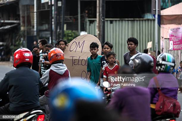Indonesian youths display 'om telolet om' posters asking for passing bus drivers to toot their horns on the side of a road on December 24 2016 in...