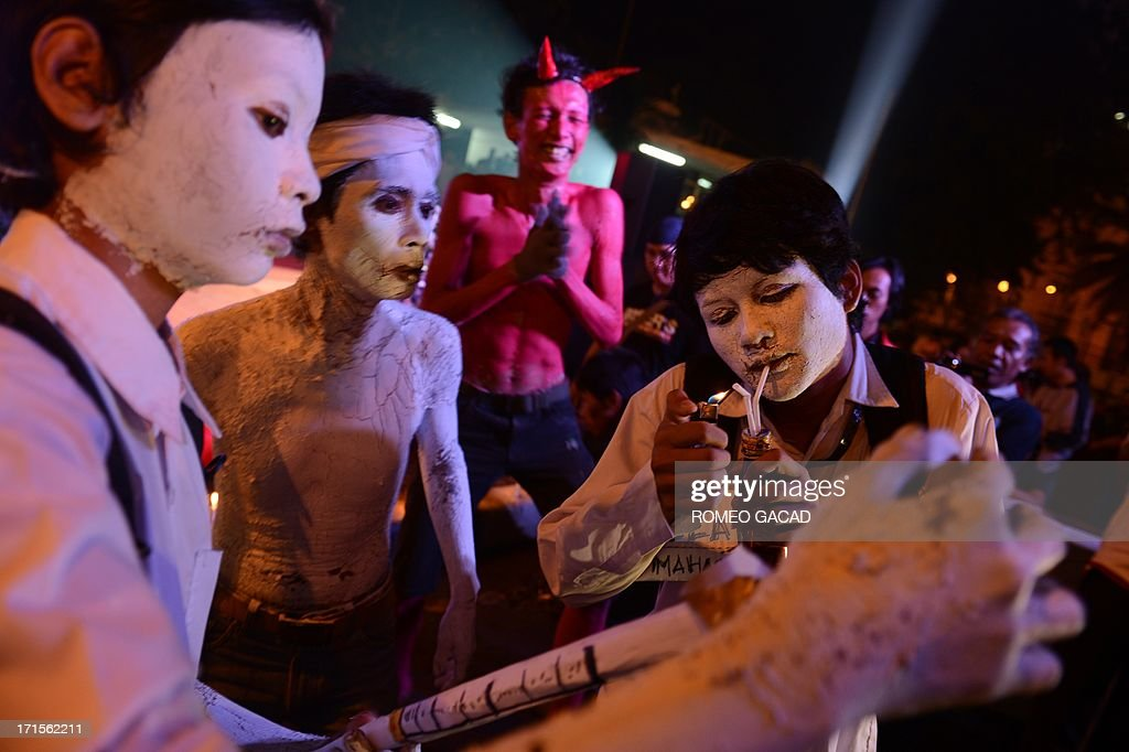Indonesian youths with painted bodies perform in a street theatre presentation about drug abuse during an anti-drug campaign programme at Jakarta's Bunderan HI monument to mark the UN's international day against drug abuse and illicit trafficking on June 26, 2013. Indonesian President Susilo Bambang Yudhoyono in his June 24, 2013 address to mark international day against drug abuse campaigned against the punishment of drug user but called for rehabilitation. According to the Ministry of Justice more than 40 percent of around 150,000 people in Indonesian prisons are detained for drug offenses.