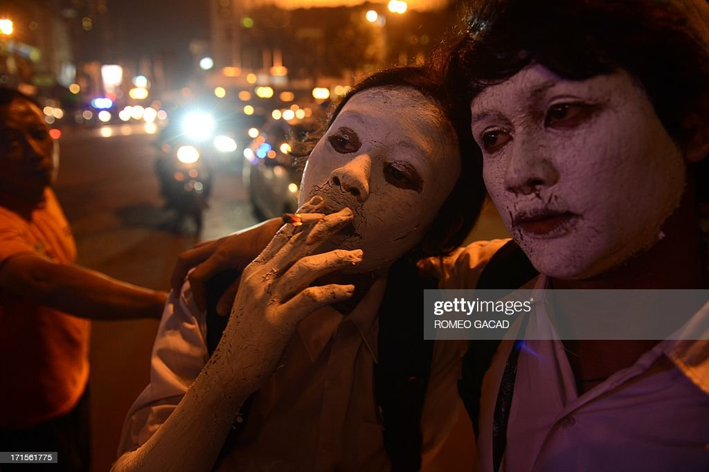 Indonesian youths with painted bodies smoke cigarette while waiting to perform in a street theatre presentation about drug abuse during an anti-drug campaign action at the Jakarta's Bunderan HI monument to mark the UN's international day against drug abuse and illicit trafficking on June 26, 2013. Indonesian President Susilo Bambang Yudhoyono in his June 24, 2013 address to mark International Day Against Drug Abuse campaigned against the punishment of drug user but called for rehabilitation. According to the Ministry of Justice more than 40 percent of around 150,000 people in Indonesian prisons are detained for drug offenses.