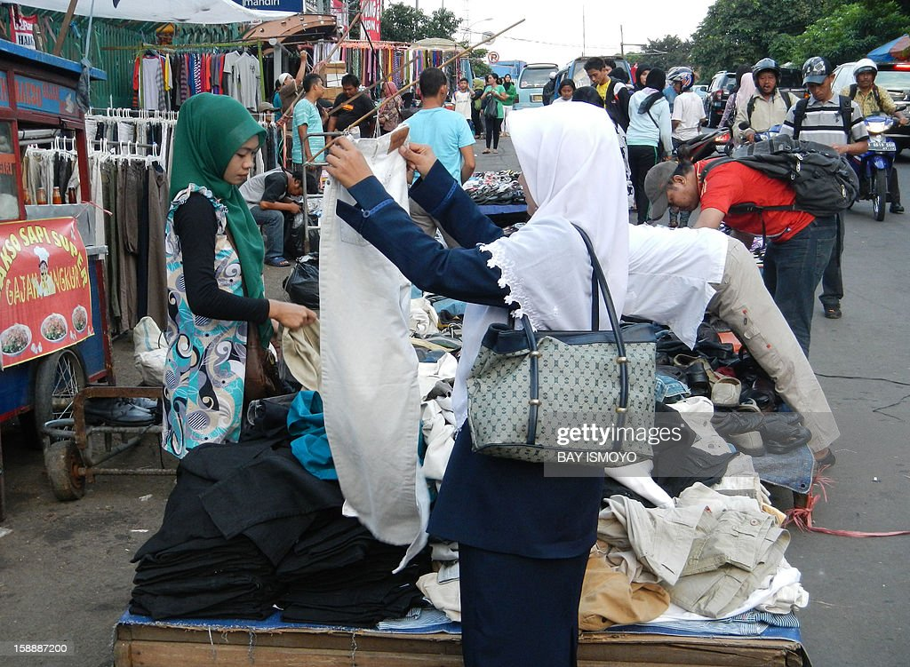 Indonesians browse street vendor stalls for clothes in Jakarta on January 3, 2013. Inflation in Indonesia slowed in December, an official said on January 3, with fuel subsidies keeping consumer prices tame throughout the year. AFP PHOTO / Bay ISMOYO