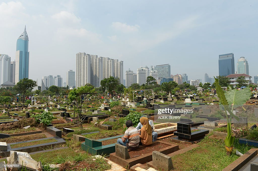 Indonesians pray at a cemetary as Muslims in the country follow a tradition of visiting the graves of loved ones ahead of the holy month of ramadan, in Jakarta on July 7, 2013. Ramadan is a holy month celebrated by Muslims worldwide marked by fasting, abstaining from foods, sex and smoking from dawn to dusk for soul cleansing and strengthening the spiritual bond between them and the Almighty.
