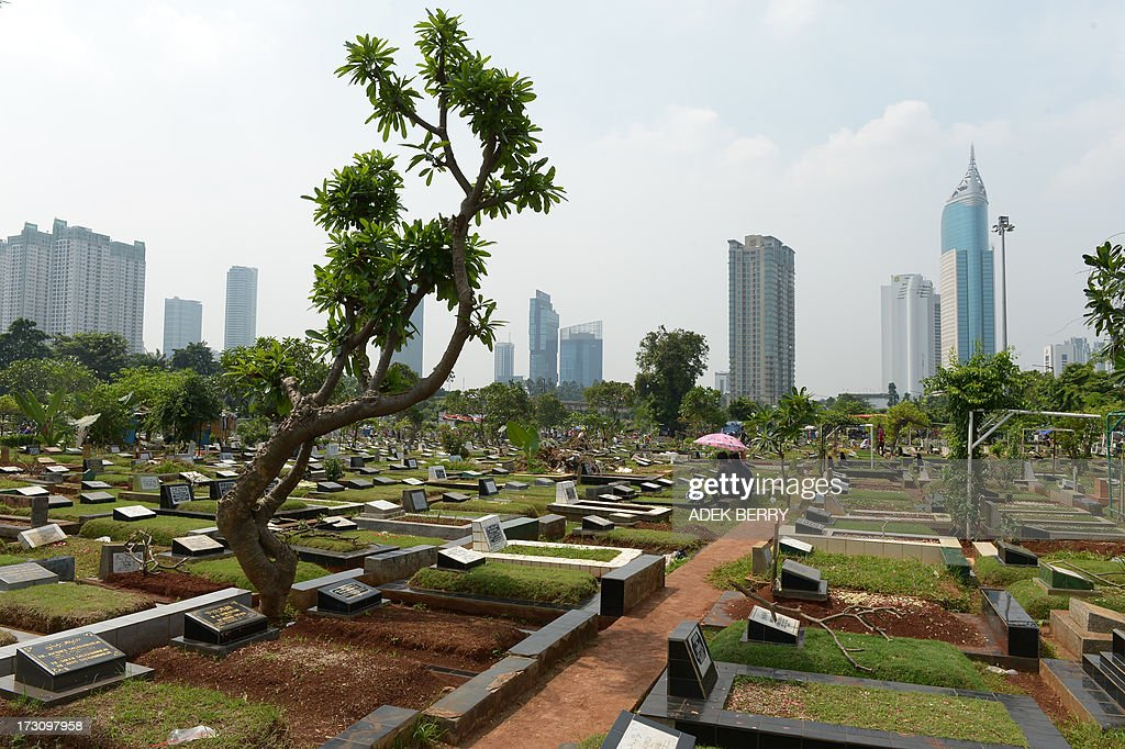 Indonesians pray at a cemetary as Muslims in the country follow a tradition of visiting the graves of loved ones ahead of the holy month of ramadan, in Jakarta on July 7, 2013. Ramadan is a holy month celebrated by Muslims worldwide marked by fasting, abstaining from foods, sex and smoking from dawn to dusk for soul cleansing and strengthening the spiritual bond between them and the Almighty. AFP PHOTO / ADEK BERRY