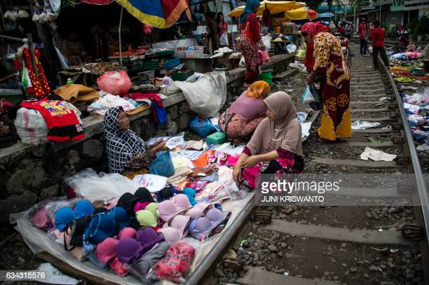 TOPSHOT Indonesians shop at a makeshift market that uses empty space along a railway line in Surabaya in eastern Java island on February 9 2017...