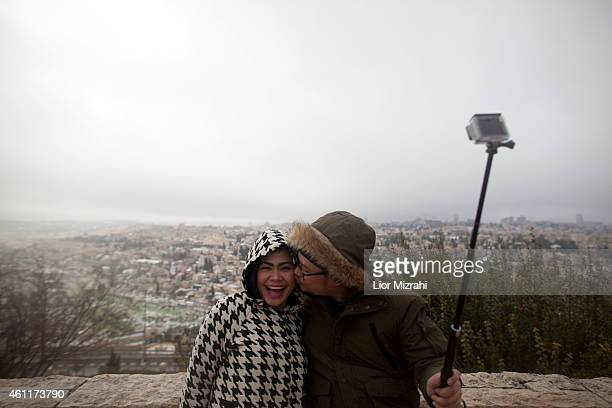 Indonesians tourists take a 'selfie' picture over the view of the snow covered Olf City on January 8 2015 in Jerusalem Israel A major storm that...
