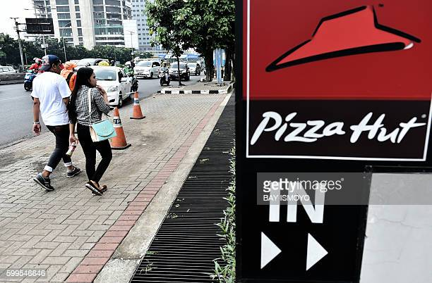 Indonesians walk past a Pizza Hut restaurant in Jakarta on September 6 2016 US chain Pizza Hut's Indonesian operation insisted its restaurants were...