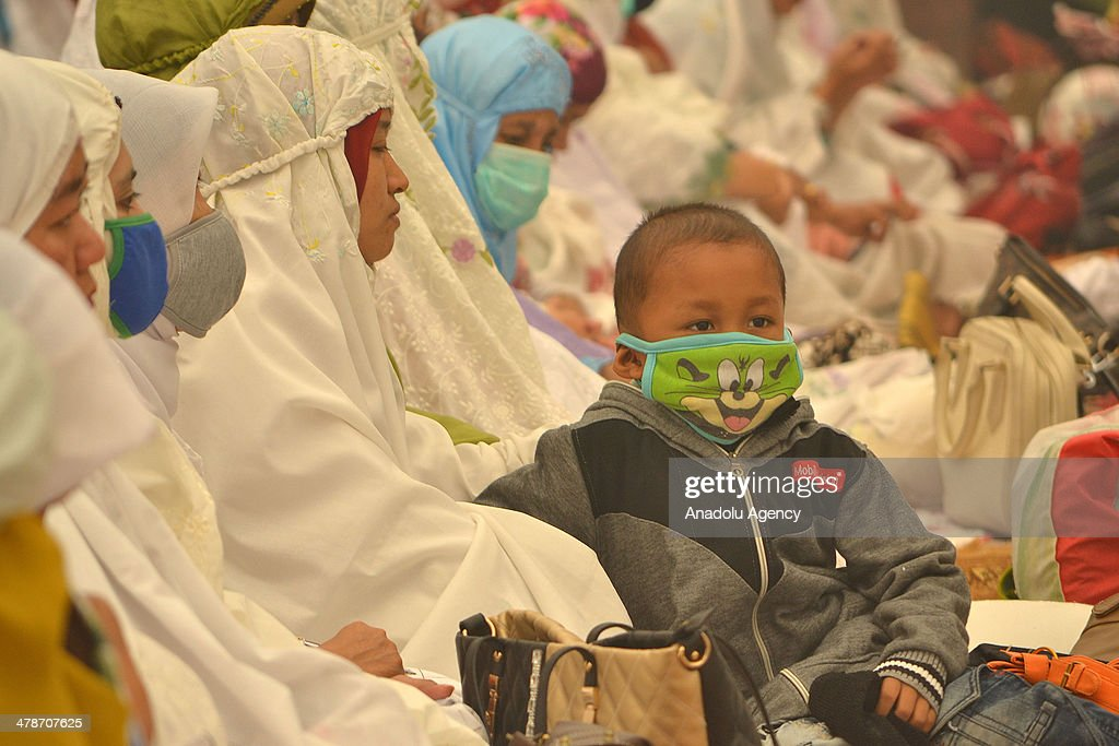 Indonesians with mask pray for rainfall to make haze disappeared on March 14, 2014 in Pekanbaru, Riau, Indonesia. Smoke haze from forest fires that still covered the Riau province causing many schools were closed and sick people breathing.