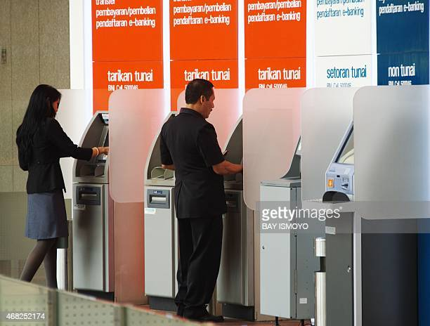 Indonesians withdraw rupiah banknotes from ATM machines in Jakarta on April 1 2015 Indonesia's Central Bank had warned that the risk of losses due to...