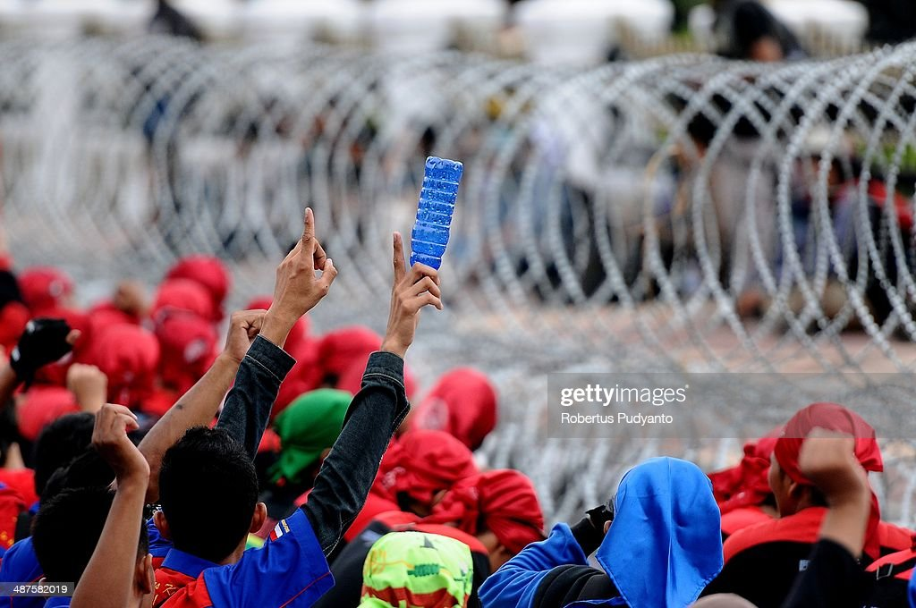 Indonesians workers sit behind barbed-wire during a protest demanding higher wages on May Day on May 1, 2014 in Surabaya, Indonesia. Protesters across Indonesia have organised rallies to demand higher wages, as Indonesia recognises its first national labour day holiday.