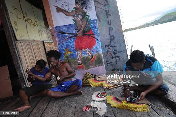 STORY 'IndonesiaPNGculturelanguage' by Jerome Rivet Photo taken on June 19 2011 shows Marco Ohee preparing a Papuan tribal costume accompanied by...