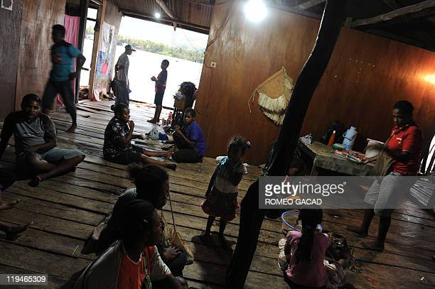 STORY 'IndonesiaPNGculturelanguage' by Jerome Rivet Photo taken on June 19 2011 shows a Papuan family as they gather in a traditional house by Lake...