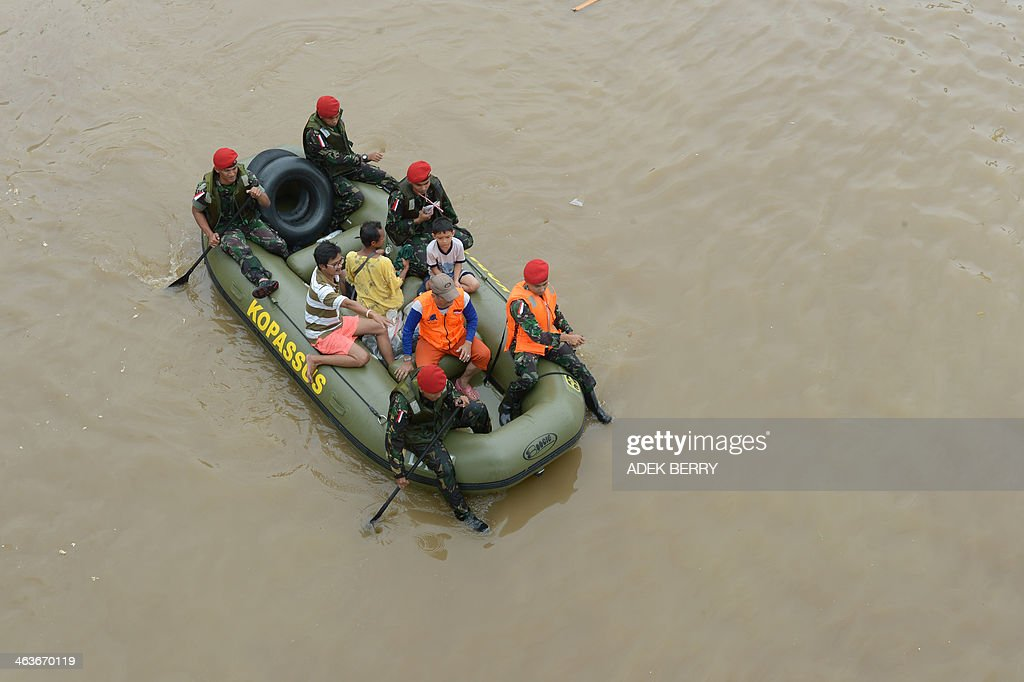Indonesia's Elite Force Kopassus (red berets) rescue standed people from their flooded houses in Jakarta on January 19, 2014. The death toll in days of floods and landslides in Indonesia has climbed to 24, an official said on January 19, as torrential rain pounded the capital.