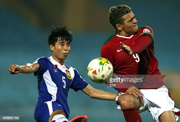 Indonesia's Gonzales fights for the ball with Laos' Khounsamnan during an AFF Suzuki Cup match against Laos at Hanoi's Hang Day stadium on November...