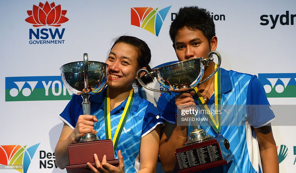Indonesia's Irfan Fadhilah (R) and partner Weni Anggraini kiss their trophies after defeating South Korea's Shin Baek Choel and Jang Ye Na in the mixed doubles final at the Yonex Australian Badminton Open in Sydney on April 7, 2013. AFP PHOTO / Saeed KHAN USE