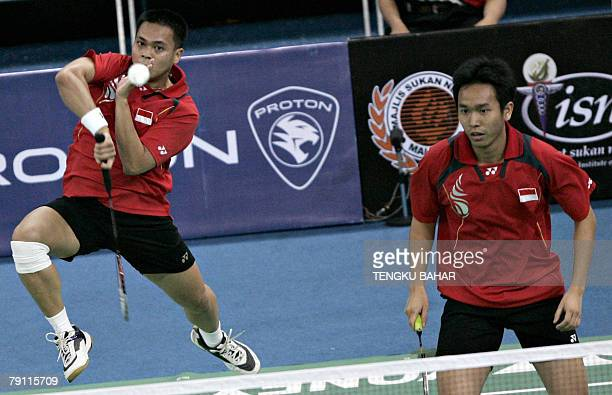 Indonesia's mens doubles pair Markis Kido smashes as Hendra Setiawan looks on as they challenge doubles pair Indonesian Candra Wijaya and US shuttler...