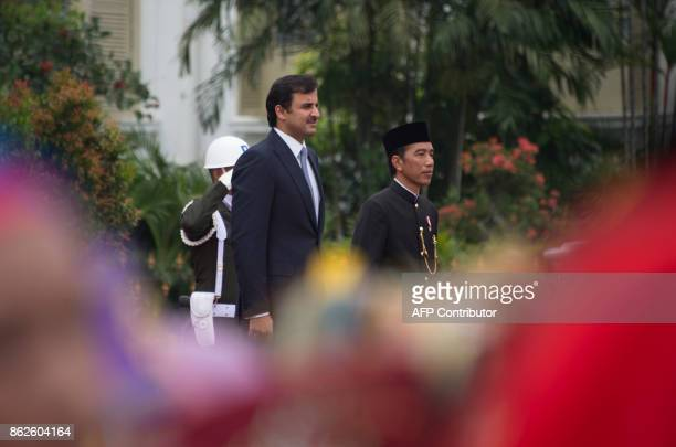 Indonesia's President Joko Widodo and Emir of Qatar Tamim bin Hamad alThani listen for the two country's anthems during a welcome ceremony by...