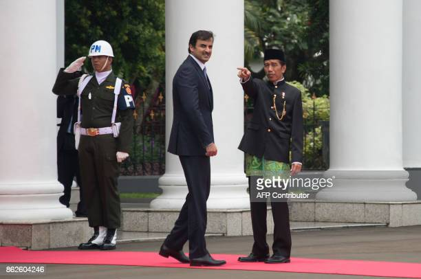 Indonesia's President Joko Widodo and Emir of Qatar Tamim bin Hamad alThani share a light moment before their meeting at the presidential palace in...