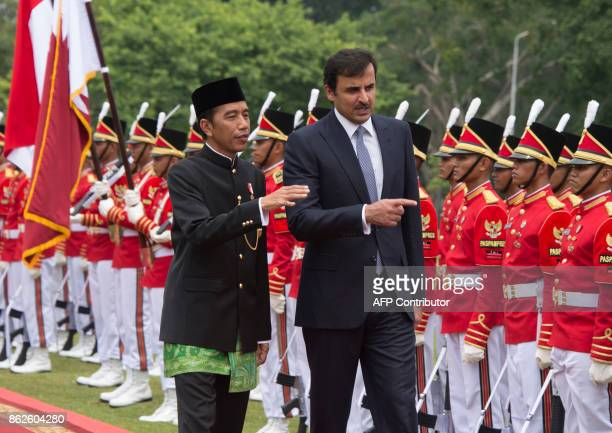 Indonesia's President Joko Widodo and Emir of Qatar Tamim bin Hamad alThani inspect the presidential honorary guard during a welcome ceremony at the...
