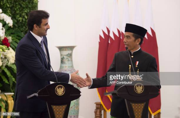 Indonesia's President Joko Widodo and Emir of Qatar Tamim bin Hamad alThani shake hands after a joint press conference at the presidential palace in...