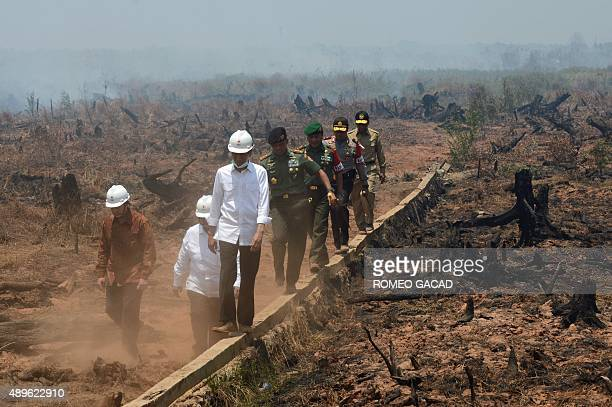 Indonesia's President Joko Widodo and officials inspect a peatland clearing near an industrial and residential area that was engulfed by fire during...