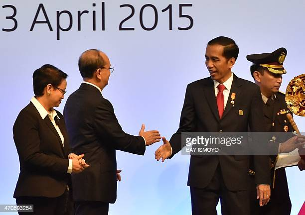 Indonesia's President Joko Widodo shakes hands with Myanmar President Thein Sein as Indonesian Foreign Minister Retno Lestari Marsudi looks on during...
