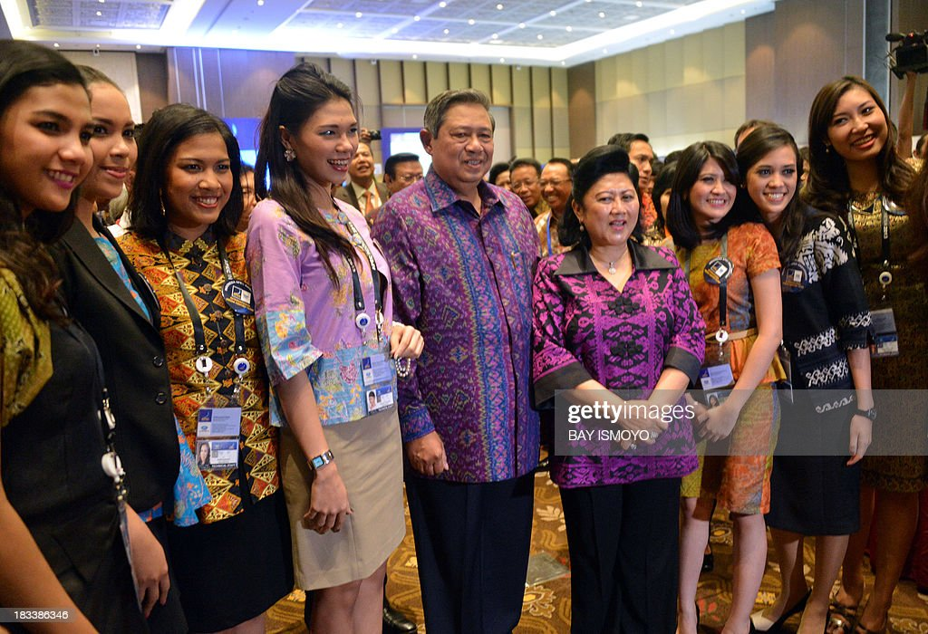 Indonesia's President Susilo Bambang Yudhoyono (centre L) and his wife Ani Yudhoyono (centre R) pose with volunteers working at the media centre at the Asia-Pacific Economic Cooperation (APEC) Summit in Nusa Dua on the Indonesian resort island of Bali on October 6, 2013. Leaders of the 21-member APEC grouping are arriving in Bali ahead of the leader's summit on October 7-8. AFP PHOTO / BAY ISMOYO