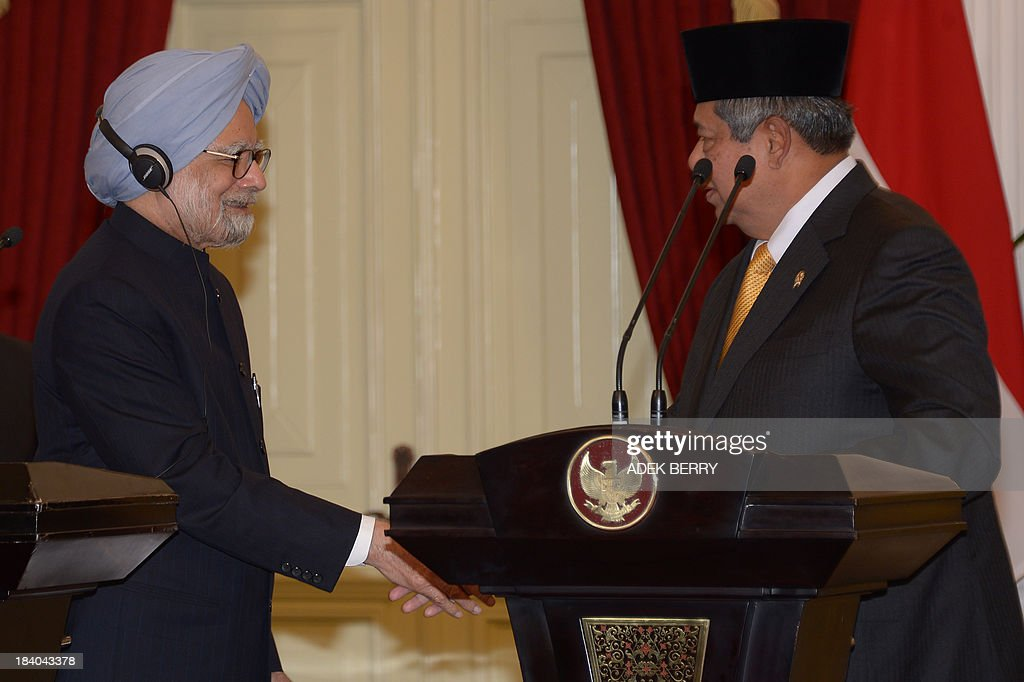 Indonesia's President Susilo Bambang Yudhoyono (R) shakes hands with India's Prime Minister Manmohan Singh (L) after a press conference at the presidential palace in Jakarta on October 11, 2013.
