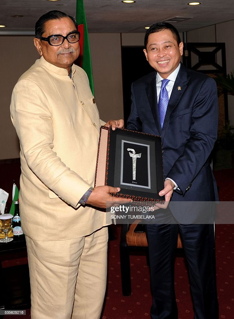 Indonesia's Transport Minister Ignasius Jonan (R) presents a traditional souvenir to Bangladeshi Minister of Civil Aviation and Tourism Rashed Khan Menon (L) following their bilateral meeting at a hotel in Kuta during the Transportation Ministerial Meeting of Developing Countries on Indonesia's resort island of Bali on May 30, 2016. The Transportation Ministerial Meeting of Developing Countries is being held in Bali from May 30-31. / AFP / SONNY