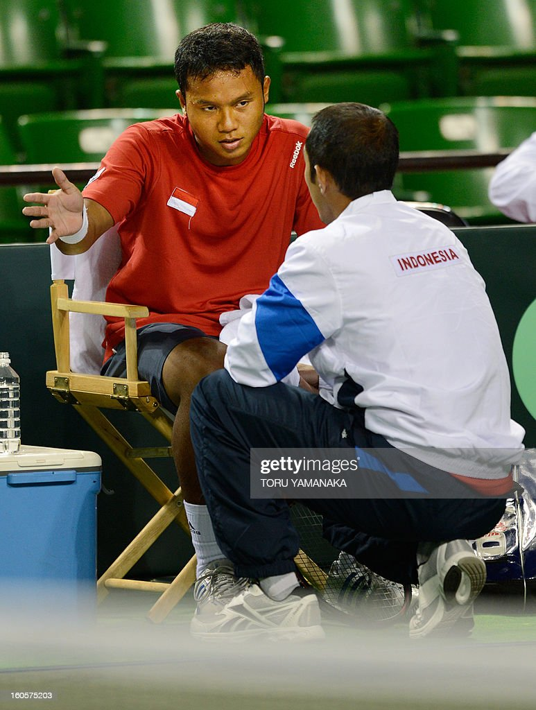 Indonesia's Wisnu Adi Nugroho (L) confers with his team captain Bonit Wirjawan (R) during his men's singles match against Japan's Yasutaka Uchiyama at the Davis Cup Asia-Oceania Zone Group I first-round tie tennis tournament on February 3, 2013. AFP PHOTO/Toru YAMANAKA