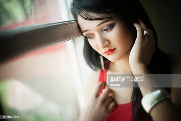 Indoor close-up of serene Asian teenager girl standing near window.