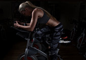 Young and attractive woman is cycling in the gym.