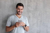 Indoor daylight picture of handsome man wearing gray casual t-shirt, laughing happily being amused by content on screen of smartphone he is holding in both hands, standing against textured wall