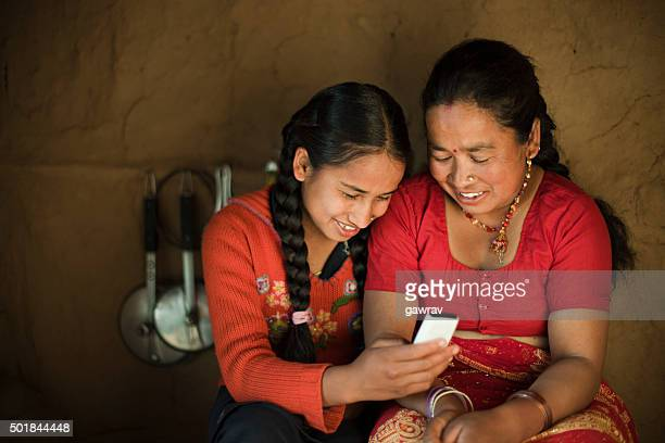 Indoor image of Asian daughter and mother sharing mobile phone.