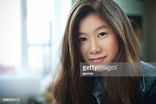 Indoor image of beautiful happy Asian girl looking at camera.