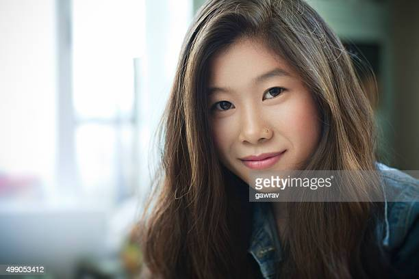 Imagen bajo techo de hermosa feliz asiática niña mirando a la cámara.