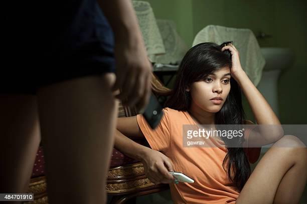 Intérieur, triste jeune fille asiatique, tenant sa tête et téléphone mobile.