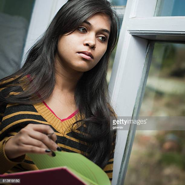 Indoor, serene Asian teenage girl student near window with book.